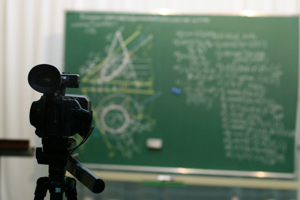 Camera pointing at a green chalkboard, streaming a maths lesson to an online audience.